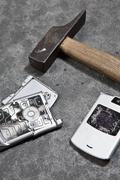 Stock Photo of A smashed mobile phone and hammer