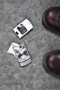 Stock Photo of Two booted feet next to a smashed mobile phone