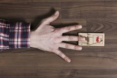 A man's finger trapped in a mousetrap, close-up of hand Stock Photos