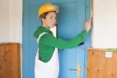 A female manual worker applying plaster to a wall - stock photo