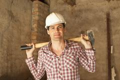 A construction worker holding a sledgehammer Stock Photos
