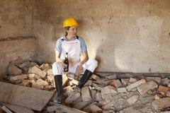 A female construction worker sitting on rubble holding a beer - stock photo