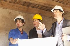Architects and a building contractor at a building site Stock Photos