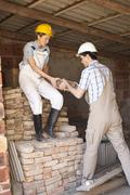 Manual workers moving bricks at a building site - stock photo