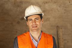 A well-dressed man wearing a hardhat and reflective vest at a building site Stock Photos
