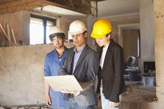 A building contractor and architects looking at a laptop at a building site Stock Photos