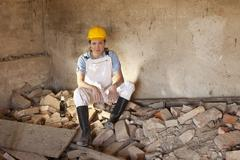 A female construction worker sitting on rubble with a beer - stock photo