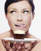 A woman holding a cupcake on a plate and licking her lips Stock Photos