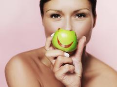 A woman holding up a green apple with bright red lipstick on it - stock photo