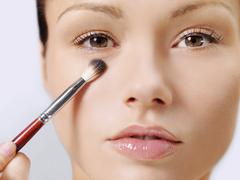 A woman applying make-up using a make-up brush Stock Photos