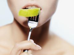 Stock Photo of A woman biting into a piece of kiwi on a fork, close-up of mouth