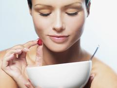 A woman holding a raspberry and looking down into a bowl Stock Photos