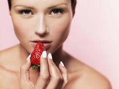 Stock Photo of A woman holding a strawberry up to her mouth
