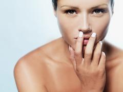 A beautiful woman with fingers covering her mouth Stock Photos