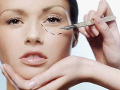 Hands holding a scalpel and a woman's face with a dotted line under her eye - stock photo