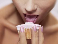 A woman licking frosting on a cupcake, focus on mouth Stock Photos