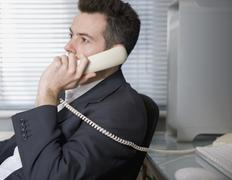 A businessman talking on a landline phone - stock photo