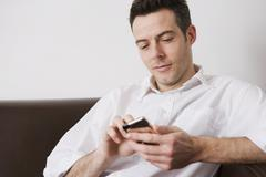 A man text messaging at home - stock photo