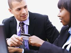 Stock Photo of A businesswoman giving a businessman a credit card