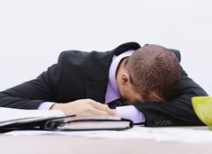 A businessman with his head down on a table, outdoors - stock photo