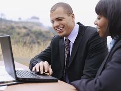A businessman and a businesswoman using a laptop together - stock photo