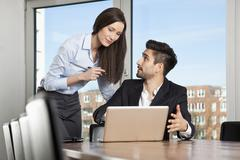 A businessman and businesswoman strategizing - stock photo