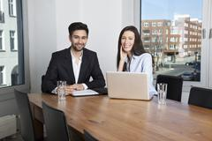 A businessman and businesswoman having a meeting in a board room Stock Photos