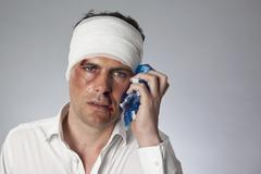 A man with bruises and a bandhead holding an ice pack to his face Stock Photos