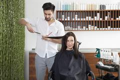 A woman having her hair cut by a male hairdresser Stock Photos