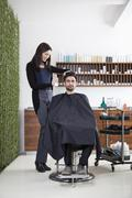 A hairdresser spraying product into a customer's hair Stock Photos