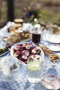 Dining table outside with focus on a dish of goat's cheese and pickled pears Stock Photos