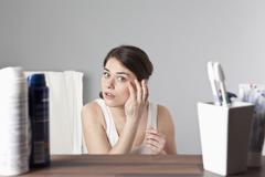 A woman inspecting her face Stock Photos