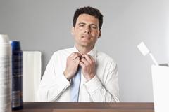 A man tying a tie in a bathroom Stock Photos