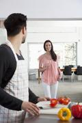 A young woman drinking wine while her boyfriend cooks, focus on woman Stock Photos
