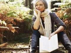 A woman in contemplation holding a book, outdoors Stock Photos