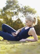 A woman in sports clothing sitting in grass reading a text message Stock Photos