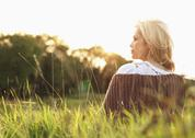 Stock Photo of A woman thinking while sitting in the grass