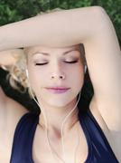 A woman wearing earphones with her eyes closed, close-up, head and shoulders Stock Photos