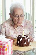 A senior woman blowing out a candle on a birthday cake Stock Photos