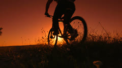 Male traveler riding mountain bike at sunrise Stock Footage
