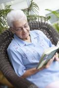 A senior woman reading in an armchair Stock Photos
