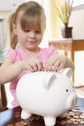 A girl putting coins into a piggy bank Stock Photos