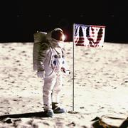 An astronaut next to an American flag on the moon - stock photo