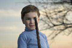 A young boy looking at a flame on the end of a stick Stock Photos