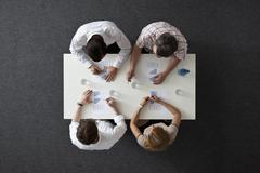 A business meeting with three businessmen and a businesswoman, overhead view - stock photo