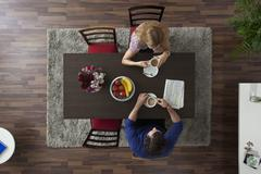 A couple having morning coffee together at a dining room table, overhead view - stock photo