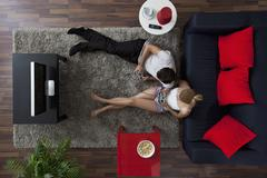 A couple playing video games in their living room, overhead view Stock Photos