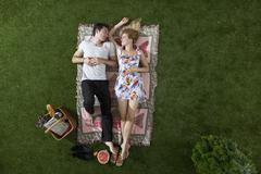A couple lying on a blanket in a park looking at each other romantically, Stock Photos