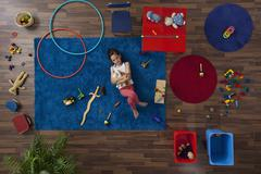 A little girl lying on a rug hugging stuffed animals, overhead view - stock photo