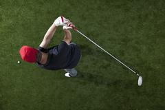 A golfer swinging a golf club, overhead view - stock photo